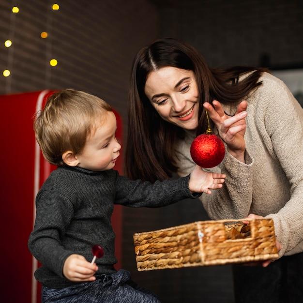 Mãe ensinando filho a decorar árvore de natal Foto gratuita