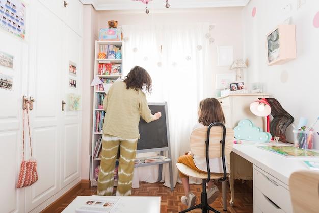 Mãe escrevendo na lousa para filha Foto gratuita