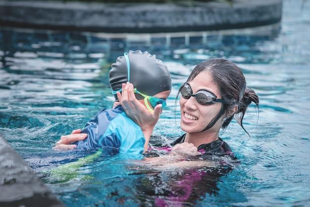 Mãe está ensinando seu filho a nadar Foto Premium