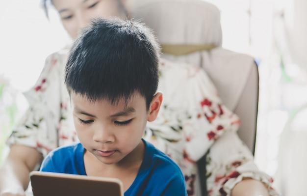 Mãe está orientando seu filho a usar o tablet da maneira certa Foto Premium