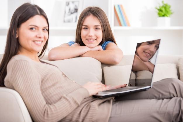 Mãe está usando o laptop enquanto está sentado no sofá. Foto Premium