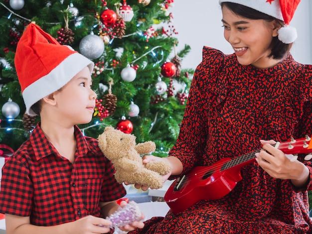 Mãe estava tocando violão no dia de natal com menino Foto Premium