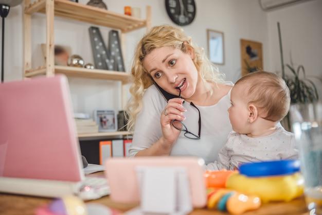 Mãe falando no telefone inteligente em casa, escritório Foto Premium