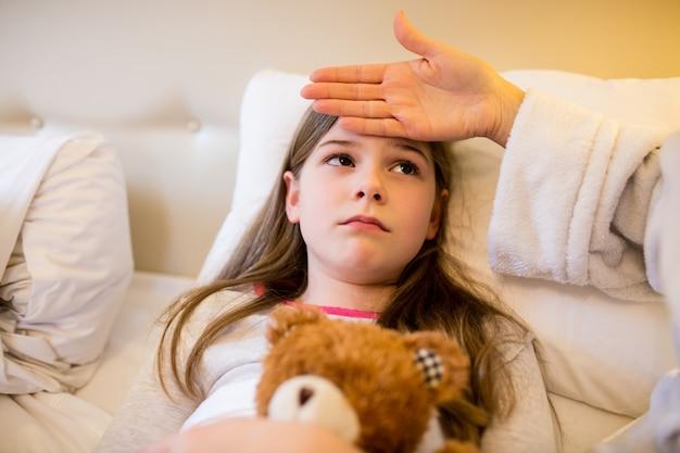 Mãe febre verificação de sua filha no quarto Foto gratuita