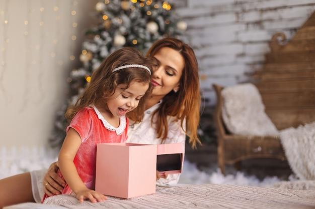 Mãe feliz com criança olhando para dentro da caixa de presente de natal mágica Foto Premium