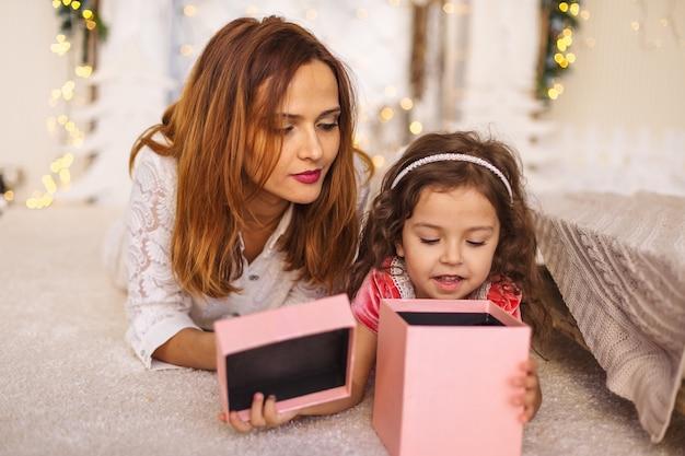 Mãe feliz com criança olhando para dentro da caixa de presente de natal Foto Premium