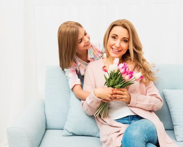 Mãe feliz com flores da filha Foto gratuita