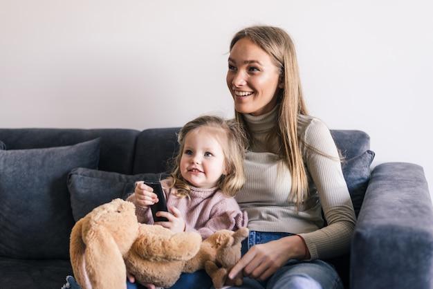 Mãe feliz com pequena filha assistindo tv usando o controle remoto Foto gratuita