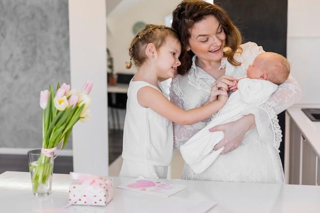 Mãe feliz com seus dois filhos bonitos em pé perto de mesa branca Foto gratuita
