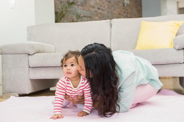 Mãe feliz com sua filha bebê no tapete na sala de estar Foto Premium