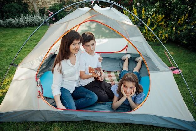 Mãe feliz com sua filha e filho na tenda na grama no parque Foto gratuita