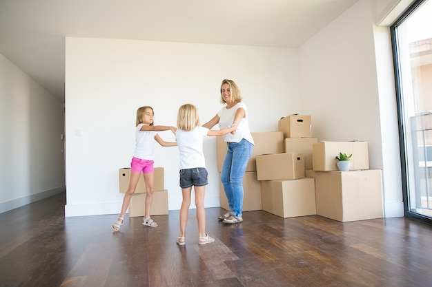 Mãe feliz dançando com duas meninas entre caixas desempacotadas Foto gratuita