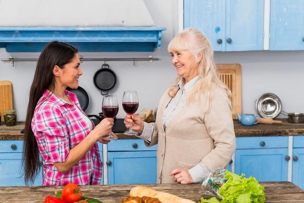 Mãe feliz e sua filha brindando com taças de vinho em pé atrás da mesa Foto gratuita