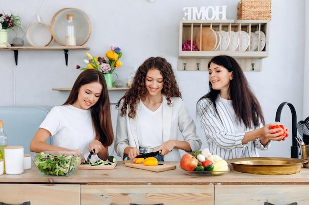 Mãe feliz lavando legumes e suas filhas juntos em uma cozinha estão preparando uma salada Foto Premium