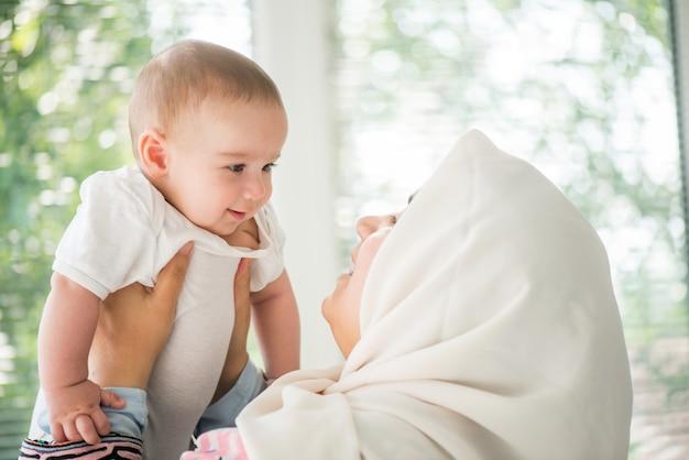 Mãe feliz segurando um bebê Foto Premium