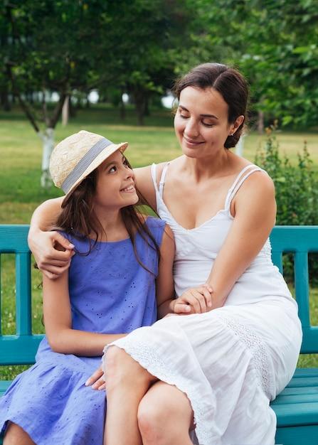 Mãe filha, abraçando, ligado, banco, ao ar livre Foto gratuita