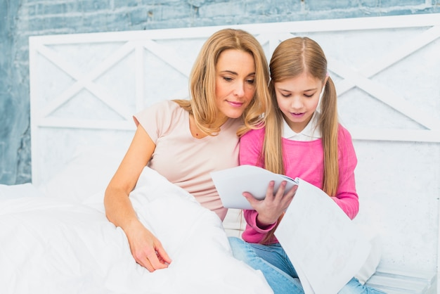 Mãe filha, cama, olhar, papeis Foto gratuita
