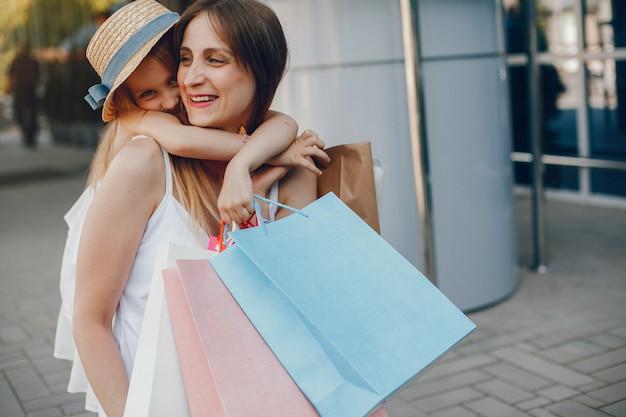 Mãe filha, com, bolsa para compras, em, um, cidade Foto gratuita