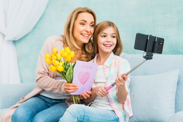 Mãe filha, com, presentes, levando, selfie Foto gratuita
