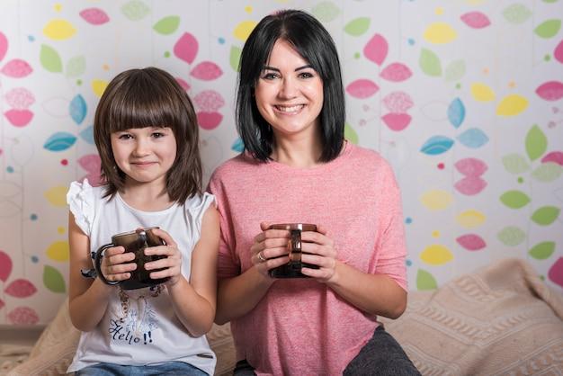 Mãe filha, com, xícaras chá Foto gratuita