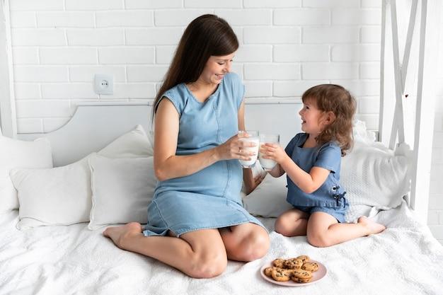 Mãe filha, comer, chocolate, biscoitos, e, bebendo, leite Foto gratuita