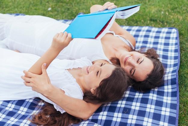 Mãe filha, deitando, e, leitura Foto gratuita