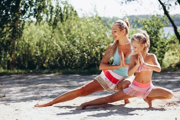 Mãe filha, em, a, praia, prática, ioga Foto gratuita