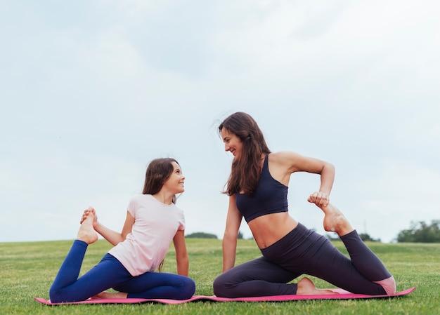 Mãe filha, fazendo, exercícios, ao ar livre Foto gratuita