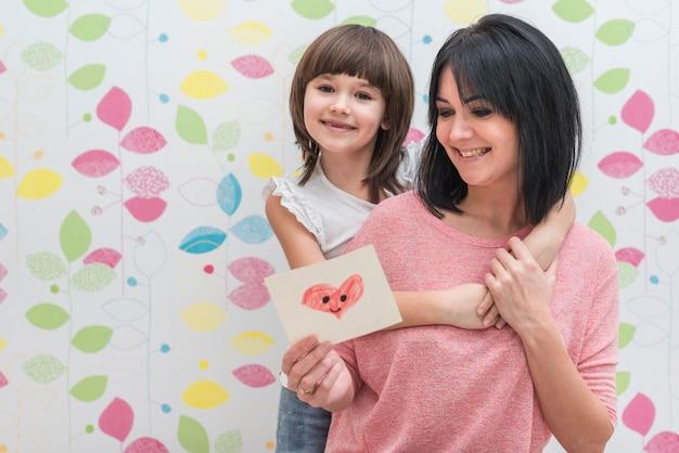 Mãe filha, leitura, pequeno, cartão cumprimento Foto gratuita