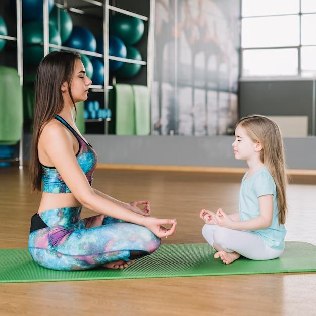Mãe filha, meditar, junto, ligado, esteira yoga, sobre, assoalho madeira Foto gratuita
