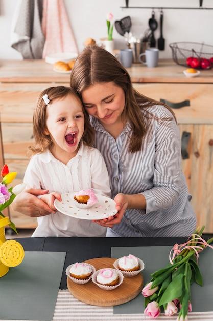 Mãe filha, prato segurando, com, cupcake Foto gratuita