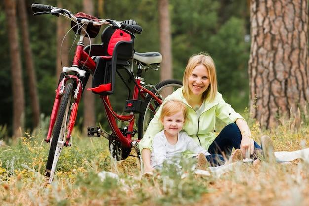 Mãe filha, relaxante, perto, bicicleta Foto gratuita