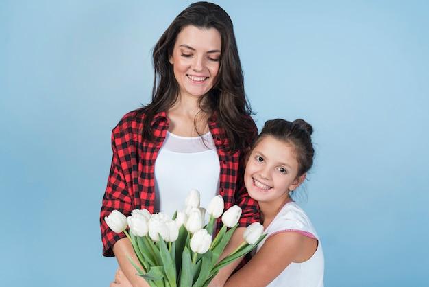 Mãe filha, segurando, branca, tulips Foto gratuita