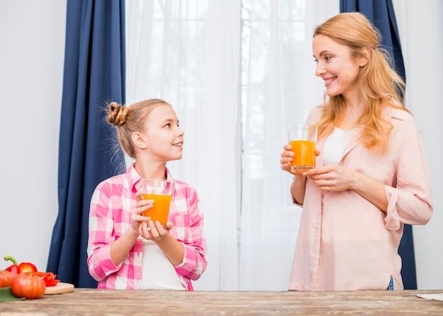 Mãe filha, segurando, copo suco, em, mão, olhando um ao outro Foto gratuita