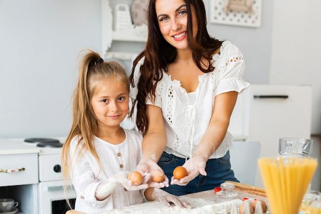 Mãe filha, segurando ovos Foto gratuita