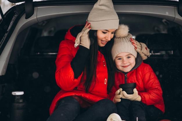 Mãe filha, sentando, carro, em, inverno Foto gratuita