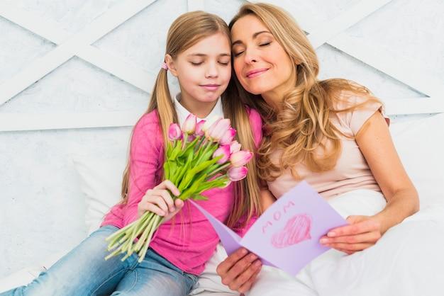 Mãe filha, sentando, com, flores, e, cartão cumprimento Foto gratuita