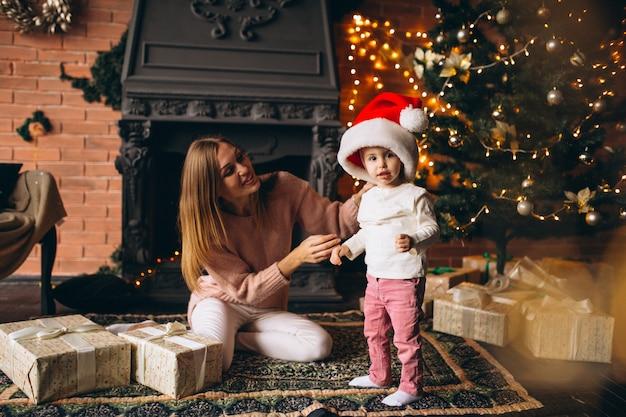 Mãe filha, sentando, por, árvore natal Foto gratuita