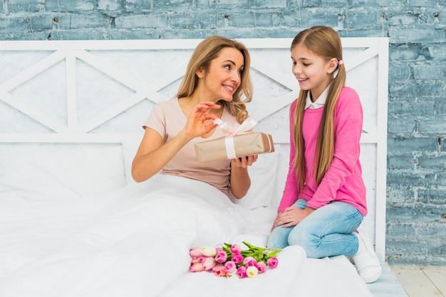 Mãe filha, sentar cama, com, caixa presente Foto gratuita