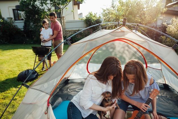 Mãe filha, tocando, com, seu, animal estimação, em, barraca Foto gratuita