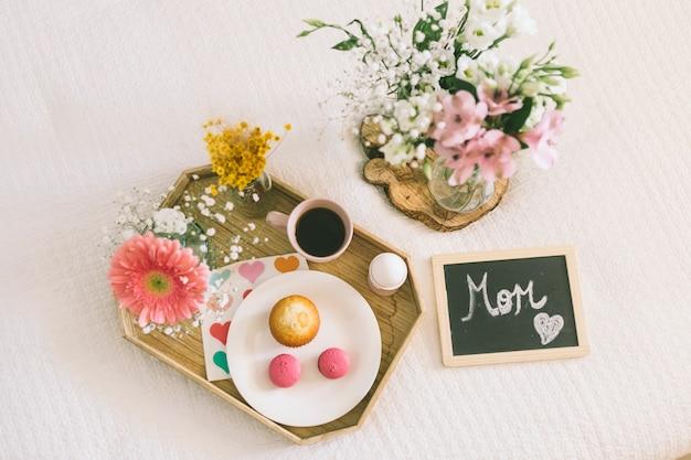 Mãe inscrição com flores e biscoitos na bandeja Foto gratuita