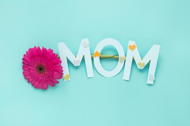 Mãe inscrição com gerbera flor na mesa Foto gratuita