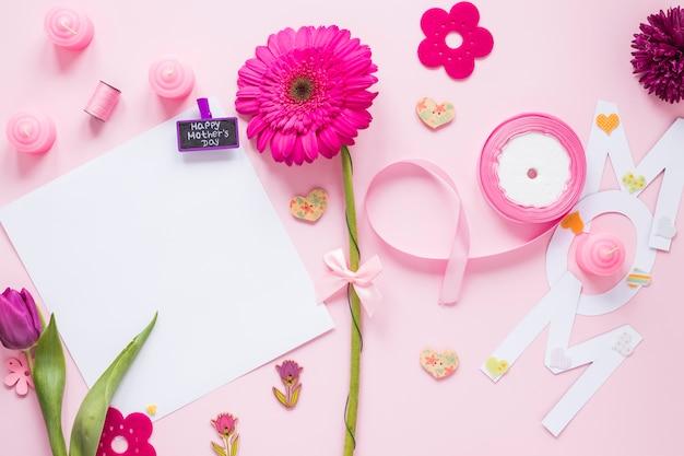 Mãe inscrição com papel e flores na mesa Foto gratuita