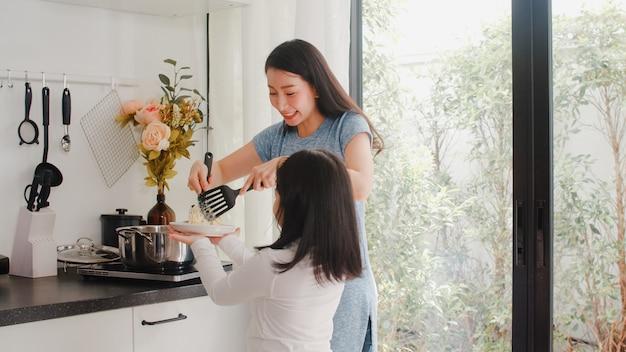 Mãe japonesa asiática nova e filha que cozinham em casa. mulheres do estilo de vida felizes fazendo macarrão e espaguete junto para a refeição do café da manhã na cozinha moderna em casa de manhã. Foto gratuita