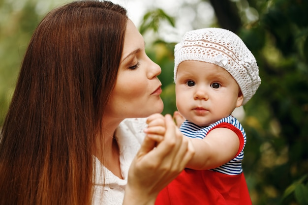 Mãe jovem amorosa, segurando e beijando seu bebê Foto Premium