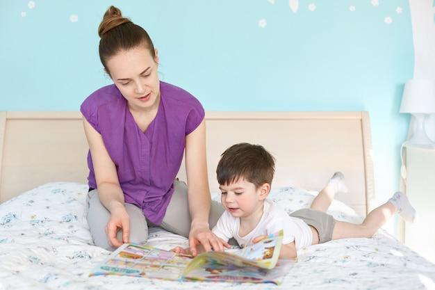 Mãe jovem carinhosa lê revista com fotos de crianças para seu filho pequeno Foto gratuita