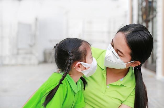 Mãe jovem, desgastar, máscara protetora, para, dela, filha, enquanto, exterior, contra, ar, poluição, em, cidade bangkok Foto Premium