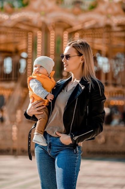 Mãe jovem elegante caminha com o bebê no parque. mãe feliz Foto Premium