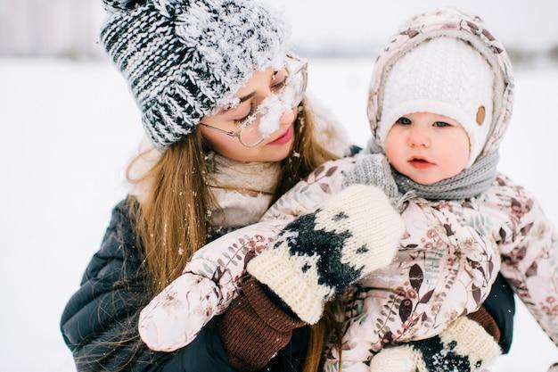Mãe jovem feliz, brincando com seu bebê adorável no campo de inverno nevado. Foto Premium