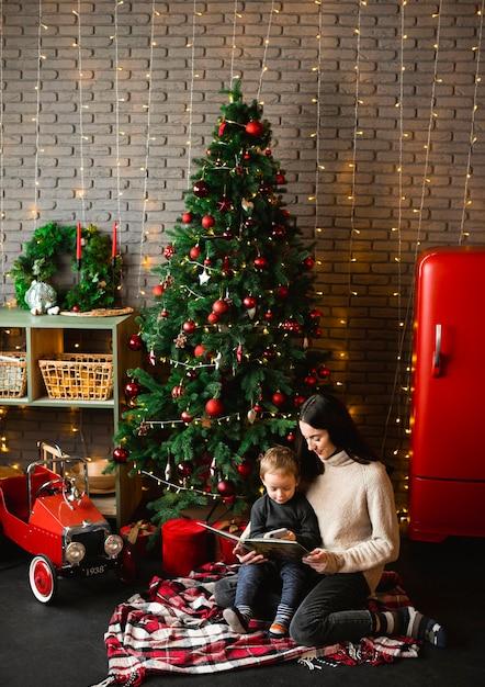 Mãe lendo história de natal para seu filho Foto Premium